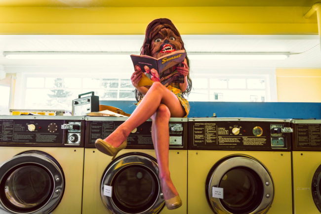 Photograph by Mako Miyamoto. Wookie girl sitting in a yellow vintage laundromat reading a Sunset Magazine