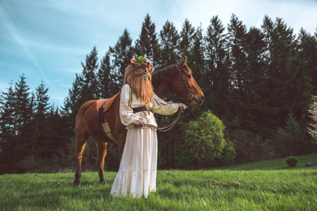 Crystal Visions I Photograph by Mako Miyamoto. Wookie in a white dress and flowers in her hair leading a horse through a magical field