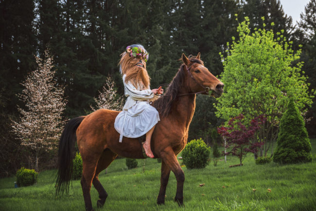 Crystal Visions III Photograph by Mako Miyamoto. Wookie in a white dress and flowers in her hair riding a horse through a magical field