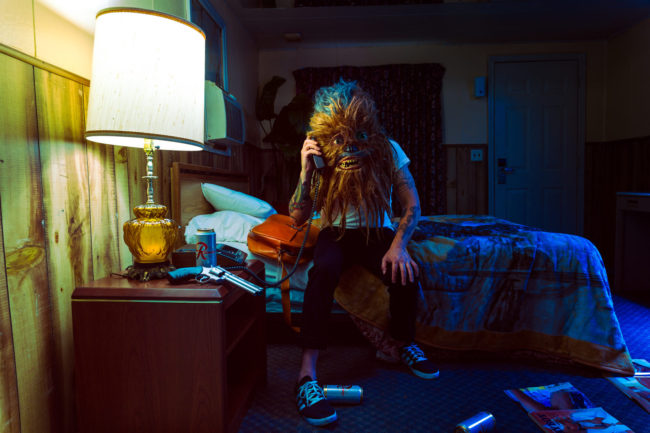 11:46 pm Photograph by Mako Miyamoto. Wookie man on the phone in a seedy motel with a gun on the nightstand. Part of the Holding Off Eternity series for a show at Gallery 135 in Portland, OR
