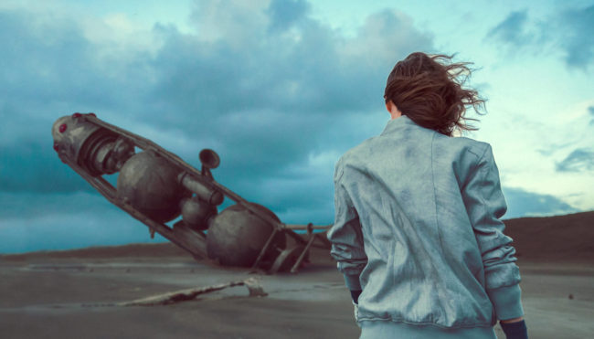 The Coast II Photograph by Mako Miyamoto. Girl walking on the oregon coast with a crashed spaceship in the sand in the background. Created for the series Further West shown at Stephanie Chefas Gallery in Portland, OR