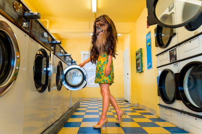 3:47 pm Photograph by Mako Miyamoto. Wookie girl in a vintage blue and yellow laundromat doing laundry in a green dress. Part of the Holding Off Eternity series for a show at Gallery 135 in Portland, OR
