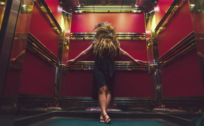 Mary Celeste V Photograph by Mako Miyamoto. Wookie woman standing in a red and gold elevator on a cruise ship